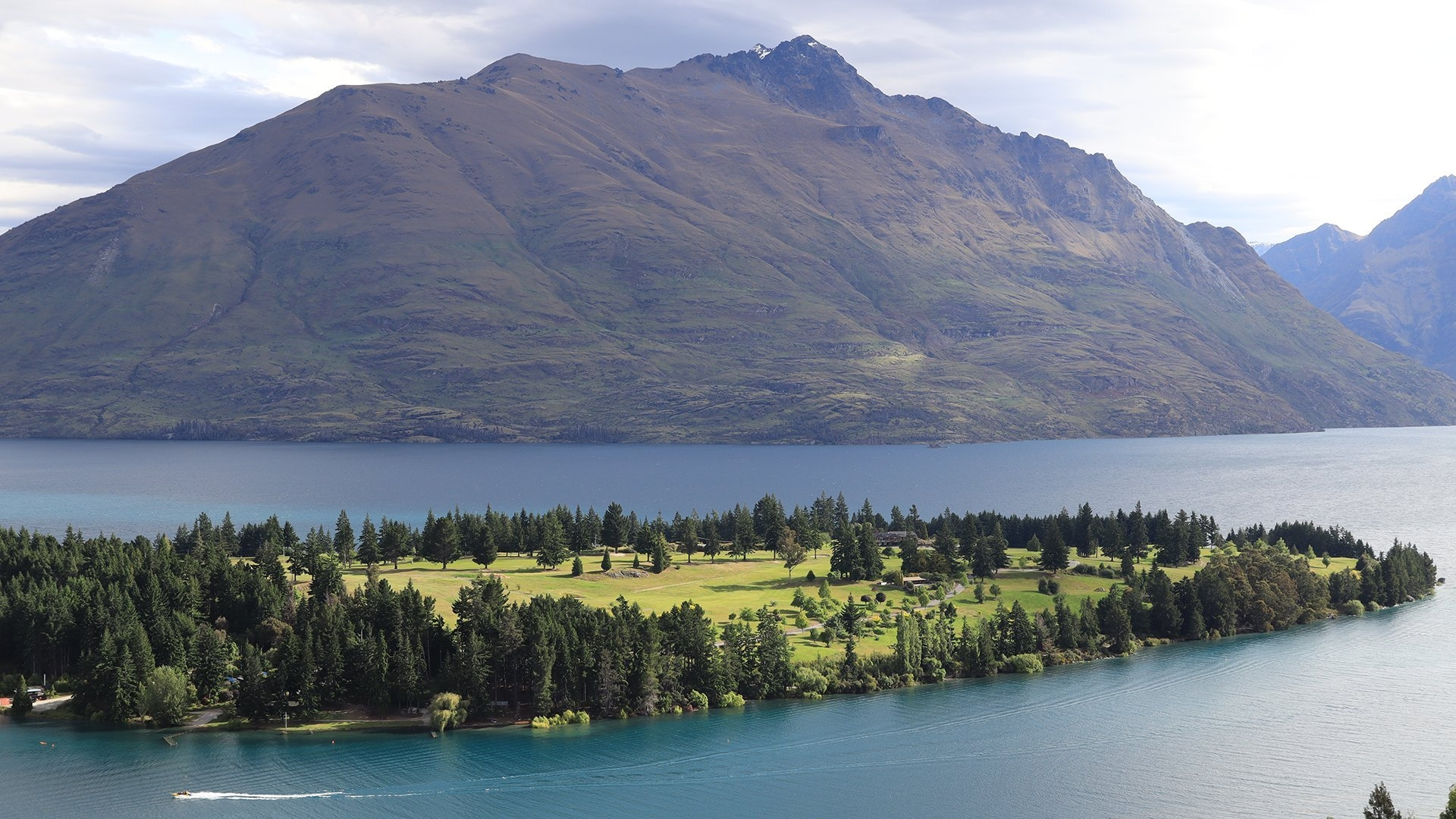 Mountains in New Zealand with a boat cruising along the lake
